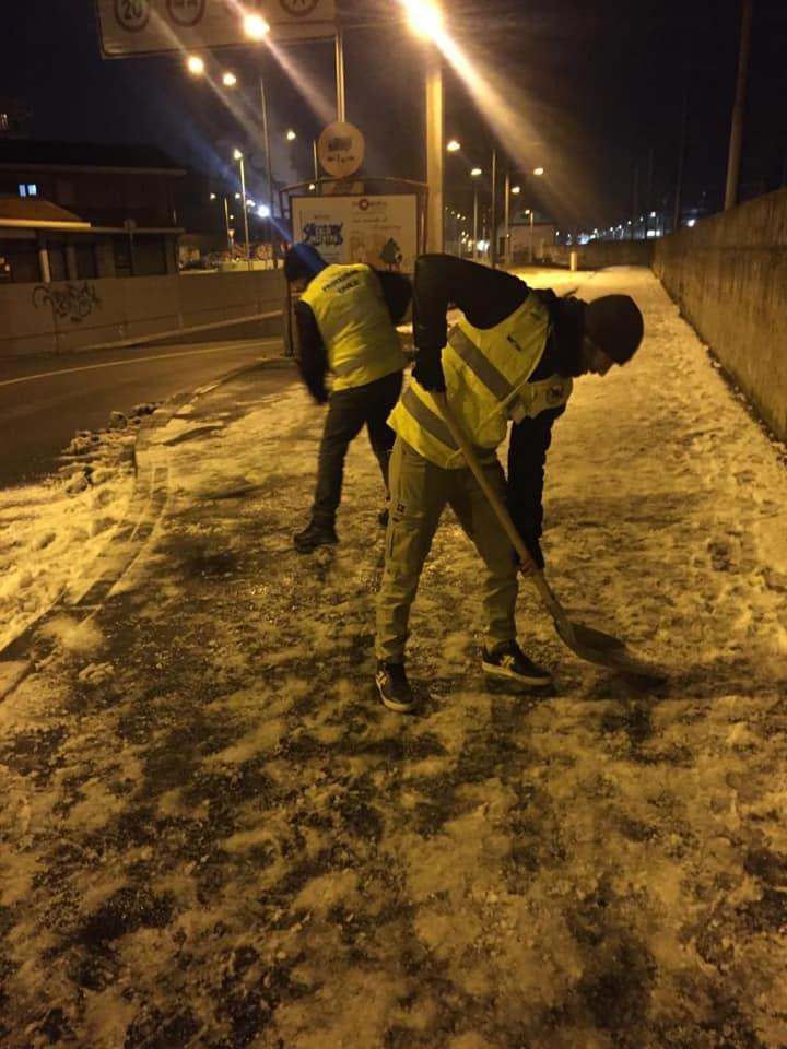 I volontari ripuliscono i marciapiedi dalla neve