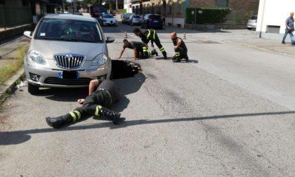 Voragine in strada sotto a un'auto